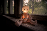 Child's doll glowing in the dust of a chernobyl window